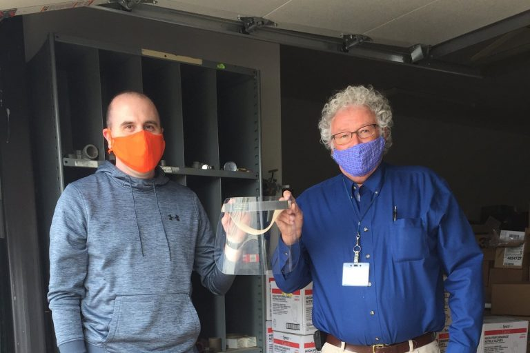Scale-Tec employees holding face shields